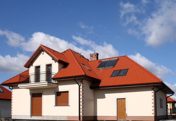 Beautiful new home with solar panels on the roof .