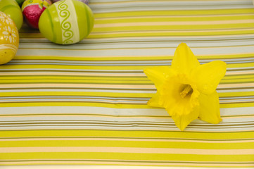 Flower head and easter eggs on a striped background.