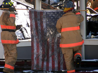 Firemen raising the American Flag after heroic firefight