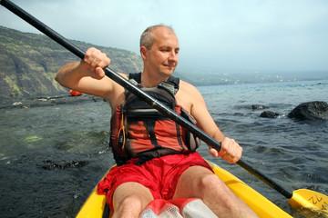 Mature man kayaking in the ocean on Big Island, Hawaii