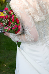 White dress of the bride and multi-coloured autumn bouquet