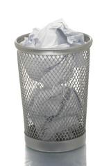 Mesh trash bin full of crampled paper