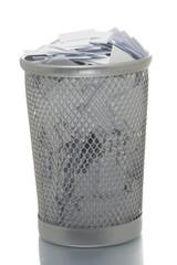 Mesh trash bin full of small paper pieces
