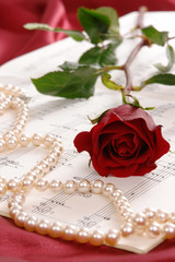 Red rose and string of pearls lying on sheet music