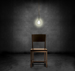 An empty chair and hannging light bulb in a dark room
