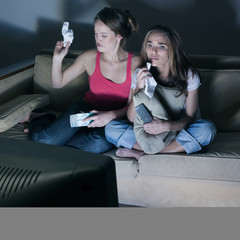 two young girls crying watching on tv  a sad movie