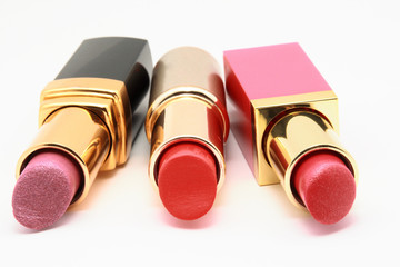 Gray, golden and pink tubes with lipsticks