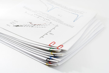 Pile of paper with graph clipping by paper clips