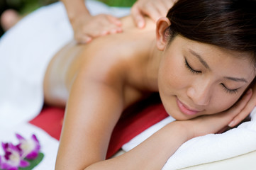 A young woman enjoying a massage outside