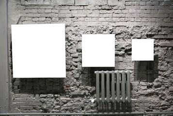 three blank frames on grey brick wall