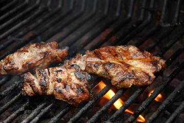 Meat cooking on barbecue grill with flames