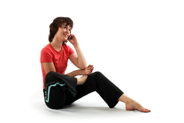 Beautiful young woman talking on mobile phone while  exercising