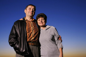Portrait of happy mature couple together outdoors at sunset