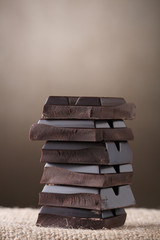 stacked pieces of CHOKOLATE on brown abstract background