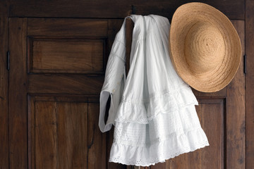 white cotton dress and straw hat on antique cabinet