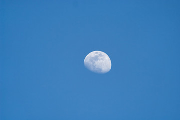 Three quarter moon in blue sky