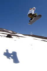 woman snowboarder in air after jump with shadow on snow