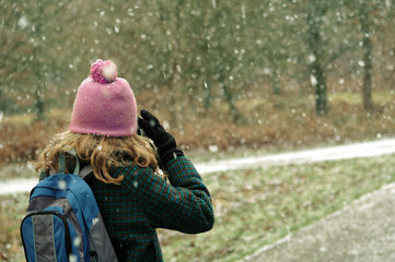 Girl taking photos of the snow