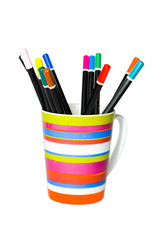 the coloured pencils in striped mug isolated