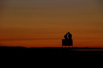 silhouettes in dusk on the beach