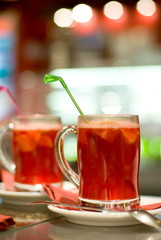 Cup of fruit tea on abstract blurred background (shallow DoF)