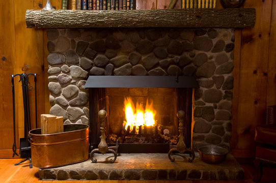 close-up of stone fireplace in log cabin with blazing fire