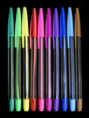 Colourful pens on a black background Back to school concept