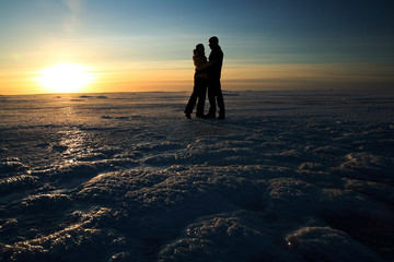 Couple holding hands against sunset on frozen sea