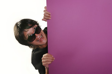 man with sunglasses holding a purple billboard