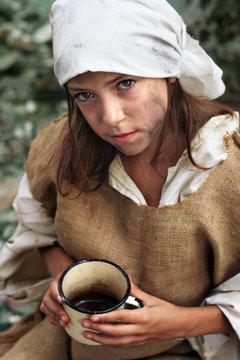 Poor little beggar girl with a vintage mug in her hand