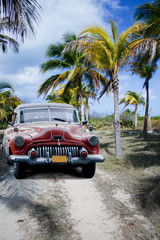 Fotorollo Autos aus Kuba Old car on a tropical beach