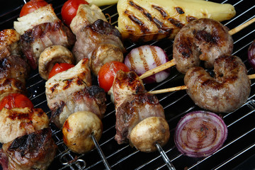 Meat, onion, cherry tomato and champignon skewers on grill