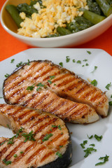 Two grilled salmon steaks with herbs close up
