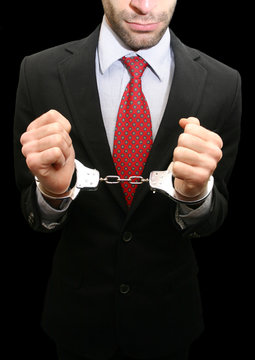 business man with red necktie and black suit in handcuffs