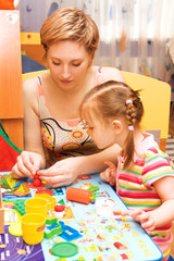 mom and daughter playing with plasticine