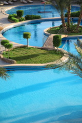 Holiday hotel and open air resort style swimming pool.
