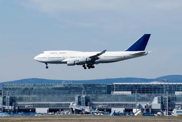Landendes Flugzeug mit Flughafengebäude