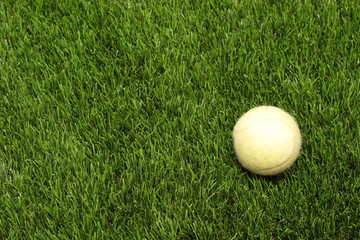 yellow tennis ball on the man-made lawn
