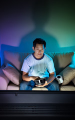 Man watching television alone at night