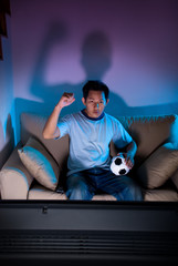 Man watching live football game on TV