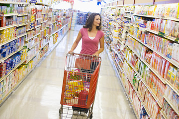 Woman pushing trolley along supermarket aisle