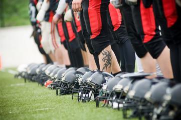 Row of football helmets and feet