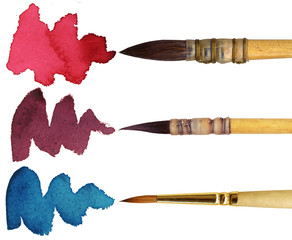 3 brushes with different colours of paint, isolated on white