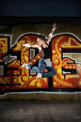 Girl break dancer jumping on a grunge graffiti wall