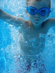 Junge taucht im Schwimmbad