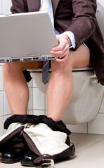 Geschäftmann mit Anzug und Computer auf Toilette