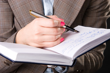 Businesswoman hand with pen and notebook