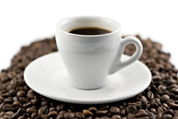 Classic white espresso cup on coffee beans