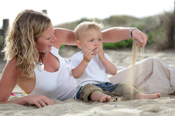 young beautiful mommy playing with her baby son on the beach