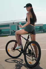 Brunette on the bicycle drink water
